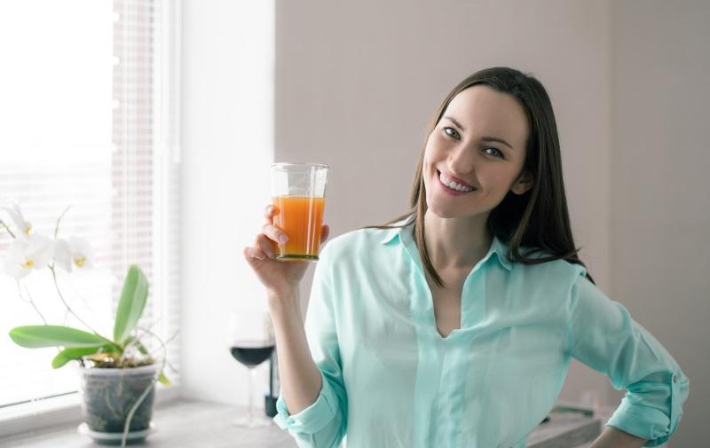 młoda kobieta stoi przy oknie i pije sok