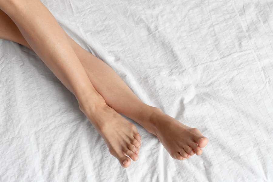 kobiece nogi bez żadnych żylaków na łóżku