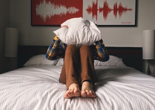 chłopak z poduszką na głowie