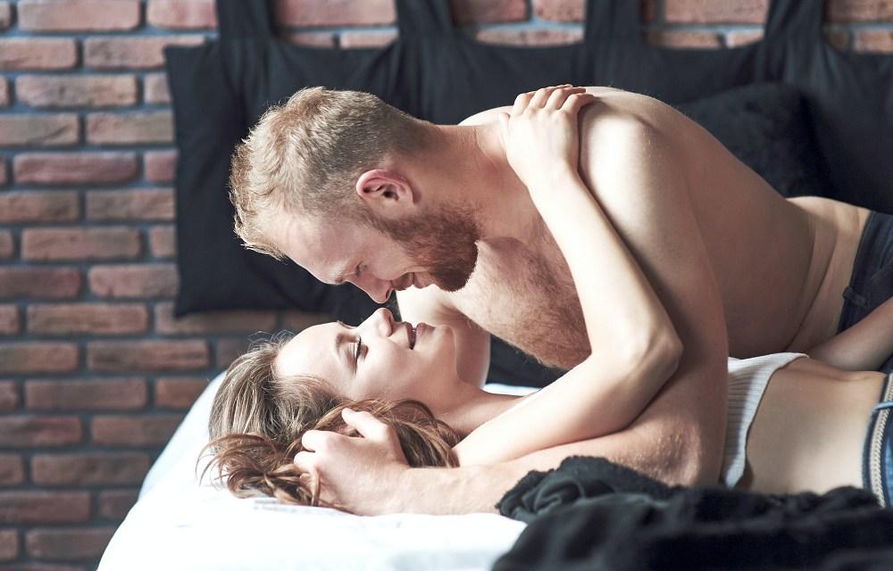 atrakcyjna para leży na łóżku namiętnie na siebie patrząc