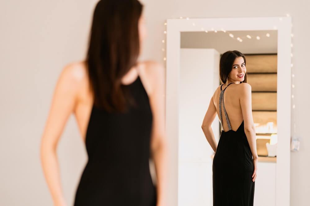 szczupła kobieta w czarnej sukience stoi tyłem do lustra